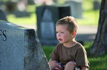 young child crying in front of tombstone