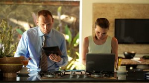 stock-footage-business-couple-with-tablet-computer-and-laptop-in-kitchen-at-home