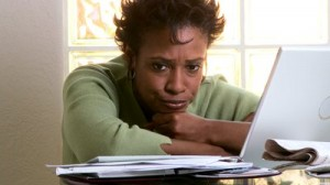 stock-footage-portrait-of-concerned-woman-with-laptop-and-bills (1)